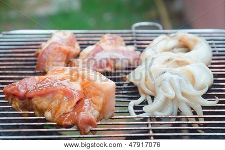 Piece Of Raw Pork Steak And Squid On Bbq Charcoal Grill