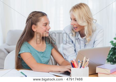 Mother and daughter using a computer to do homework