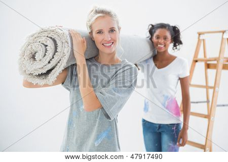 Smiling housemates carrying rolled up rug and looking at camera in new home