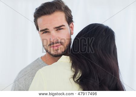 Woman giving hug to uninterested boyfriend looking at camera