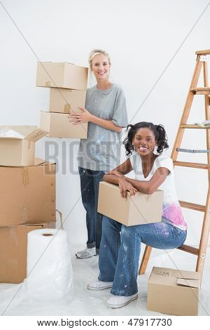 Cheerful housemates carrying cardboard moving boxes and smiling at camera in new home