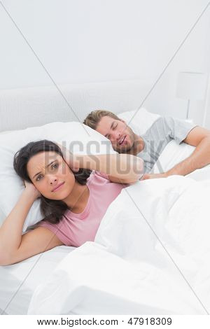 Woman covering her ears while her husband is snoring next to her