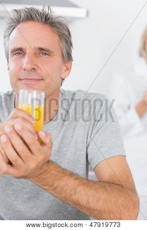 Cheerful man drinking orange juice in kitchen with partner standing behind