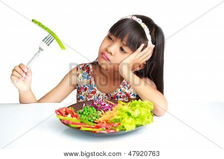 Little Asian Girl With Expression Of Disgust Against Broccoli
