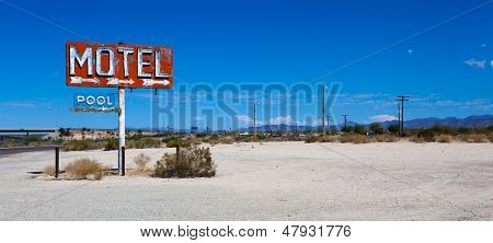 A vintage neon motel sign in the desert with a sky blue background