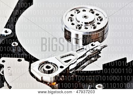 Close-up of an hard disk drive and a binary code overlay