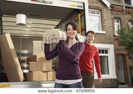 Portrait of happy young couple carrying rolled carpet by moving van