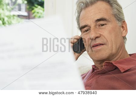 Closeup of a middle aged man using cell phone and looking at bill
