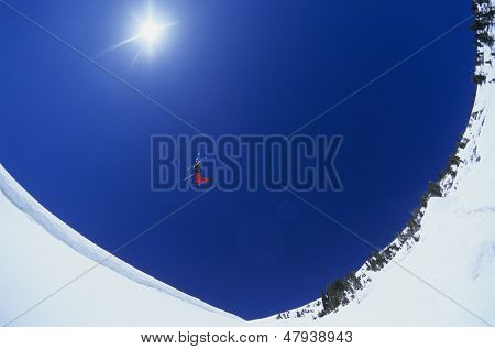 Low angle view of skier performing flip on snow mountain with clear blue sky in background