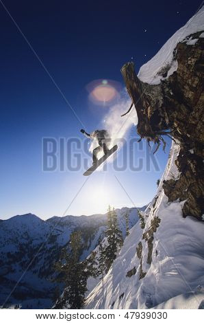 Low angle view of snowboarder jumping from mountain ledge
