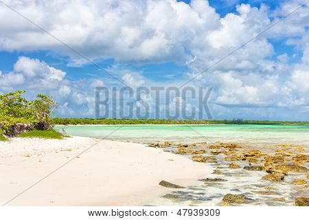 Deserted tropical beach at Cayo Coco (Coco key) in Cuba on a beautiful day with puffy white clouds on a blue sky