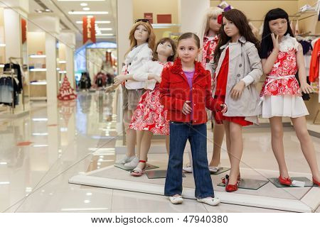 MOSCOW - MAR 18: Little Jeanette 6 years trying on clothes together with mannequins in the large store children clothes Jakimanka on March 18, 2012 in Moscow, Russia.
