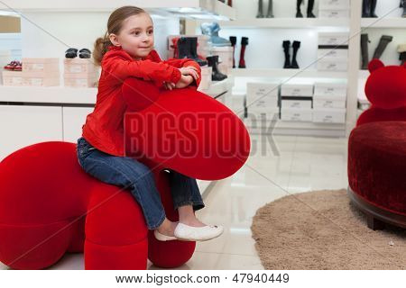 MOSCOW - MAR 18: Smiling Jeanette 6 years old having fun in a big red toy at the store childrens shoes Jakimanka on March 18, 2012 in Moscow, Russia.