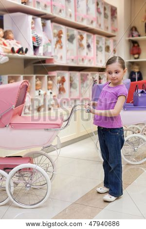 MOSCOW - MAR 18: Jeanette 6 years old in a toy storewith rows of dolls purchased a buggy in a children store Jakimanka on March 18, 2012 in Moscow, Russia.