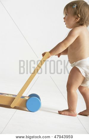 Side view of cute baby girl pushing cart isolated on white background