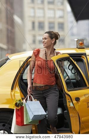 Smiling young woman with shopping bags exiting yellow taxi