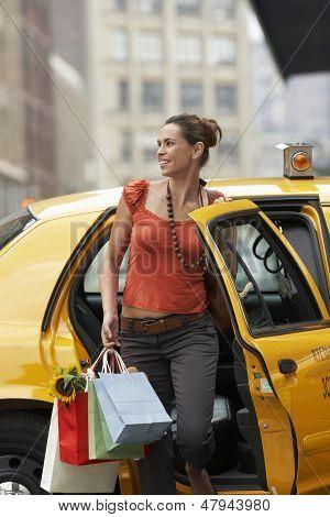 Sonriente a joven con bolsas de compras, salir del taxi amarillo