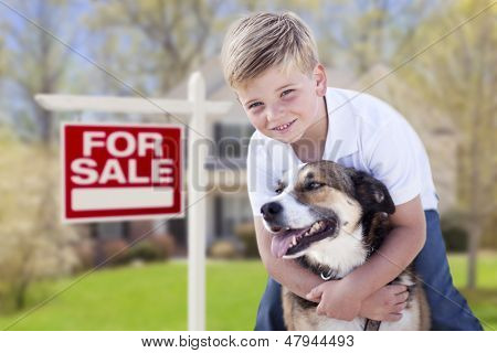 Happy Young Boy and His Dog in Front of For Sale Real Estate Sign and House.