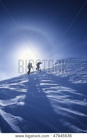 Low angle view of skiers hiking to mountain summit