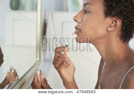 Closeup of an African American woman applying lip gloss in mirror at home