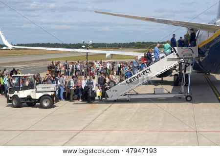 WEEZE, GERMANY - JUNE 29: People waiting in queue during the boarding to the Ryanair plane in Weeze airport, Germany on June 29, 2013. Ryanair will carry 81.5 million passengers this year