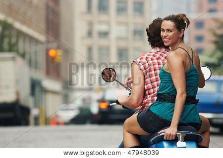 Rear view portrait of a couple riding on moped in street