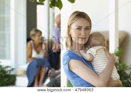 Portrait of young mother carrying baby on porch with grandparents behind