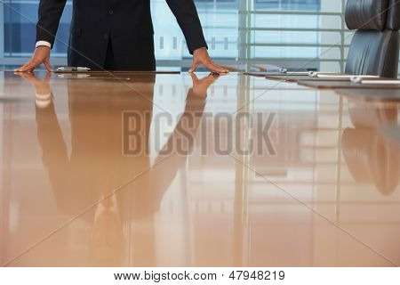 Midsection of a businessman standing with hands on conference table
