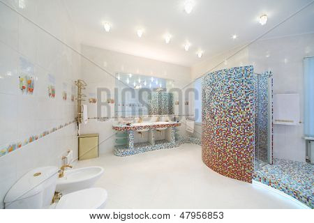 Light and clean bathroom with toilet, bidet, shower cabin with blue tiles.