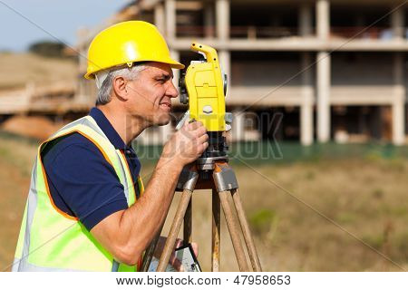 Senior land surveyor working with theodolite at construction site
