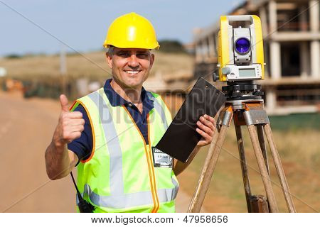 senior surveyor giving thumb up on construction site