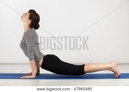 Young woman exercising yoga in a gym
