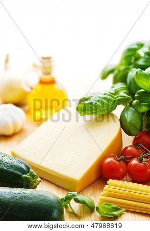 Pedaço de queijo gouda com ingredientes de massas, incluindo tomate, abobrinha, folhas de manjericão, azeite,