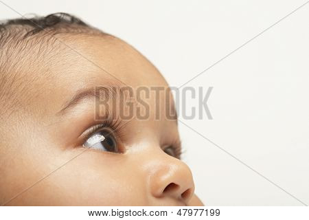 Closeup of baby boy looking up on white background