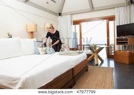 Hotel Chambermaid Making Guest Bed