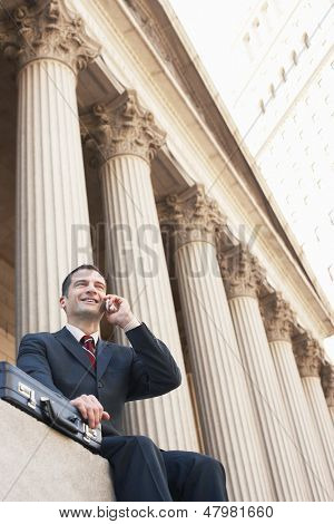Low angle view of a successful lawyer using mobile phone outside courthouse