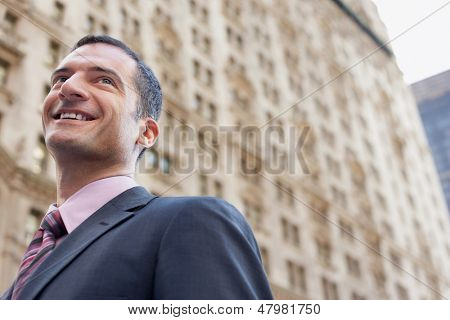 Low angle view of a businessman smiling against blurred building