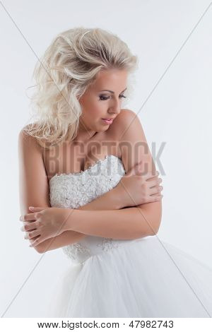 Shy beautiful bride posing in studio, close-up