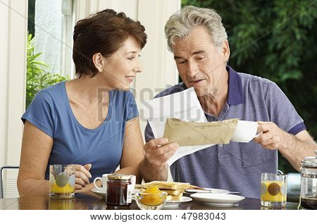 Middle aged couple looking at bills over breakfast in the house