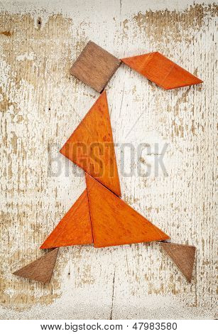 abstract figure of a walking or running girl built from seven tangram wooden pieces, a traditional Chinese puzzle game; rough white painted barn wood background