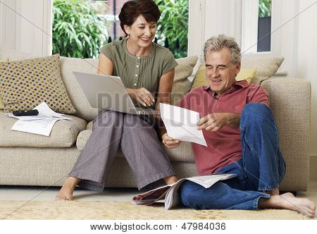 Middle aged couple looking at bill and laptop in the living room