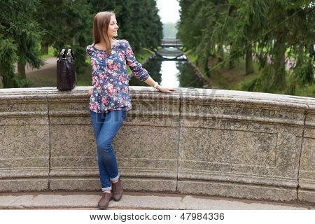 Beautiful Young Girl On The Old Stone Bridge