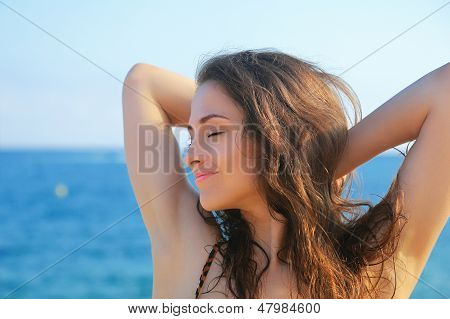 Beautiful Woman Relaxing With Closed Eyes On Blue Sea Background