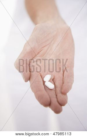 Closeup of a hand holding out two pills