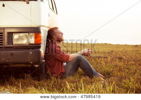 Driver Resting In A Field Near His Car