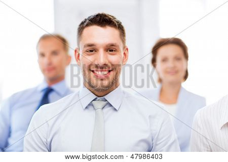 business concept - smiling handsome businessman with team in office