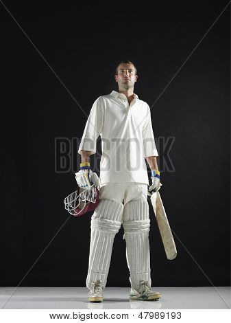 Full length of a cricket player holding bat and helmet against black background