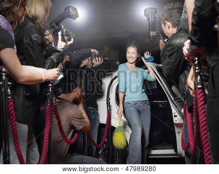 Excited woman with cleaning equipment getting out of limousine in front of paparazzi