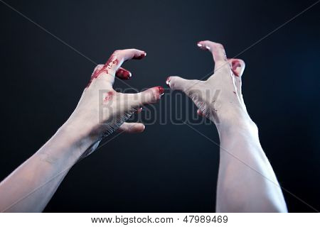 Grey skin bloody zombie hands, studio shot over gray background