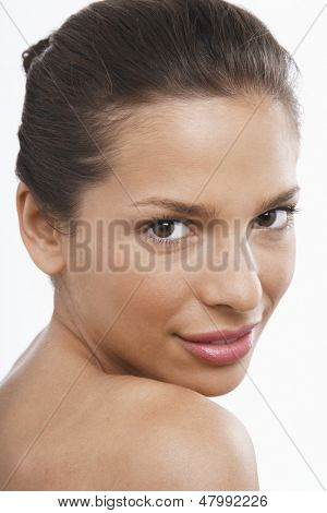 Closeup portrait of attractive young woman looking over shoulder on white background